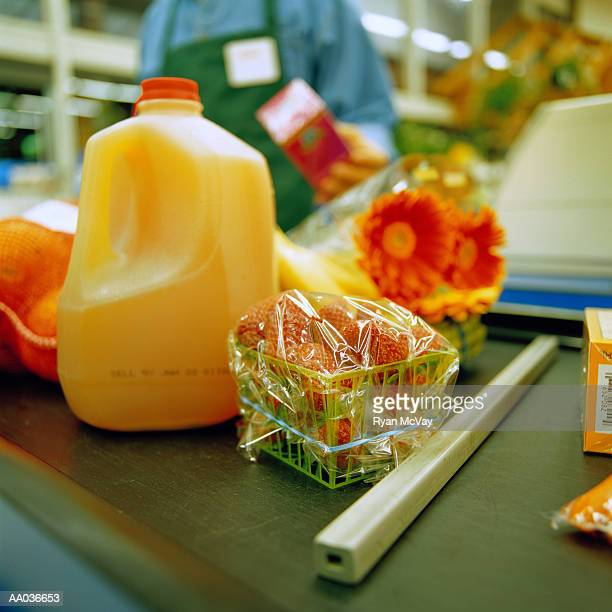 Groceries on conveyor belt at checkout counter, close-up