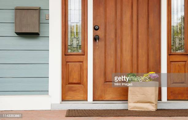 grocery bag on front stoop - front door stock pictures, royalty-free photos & images