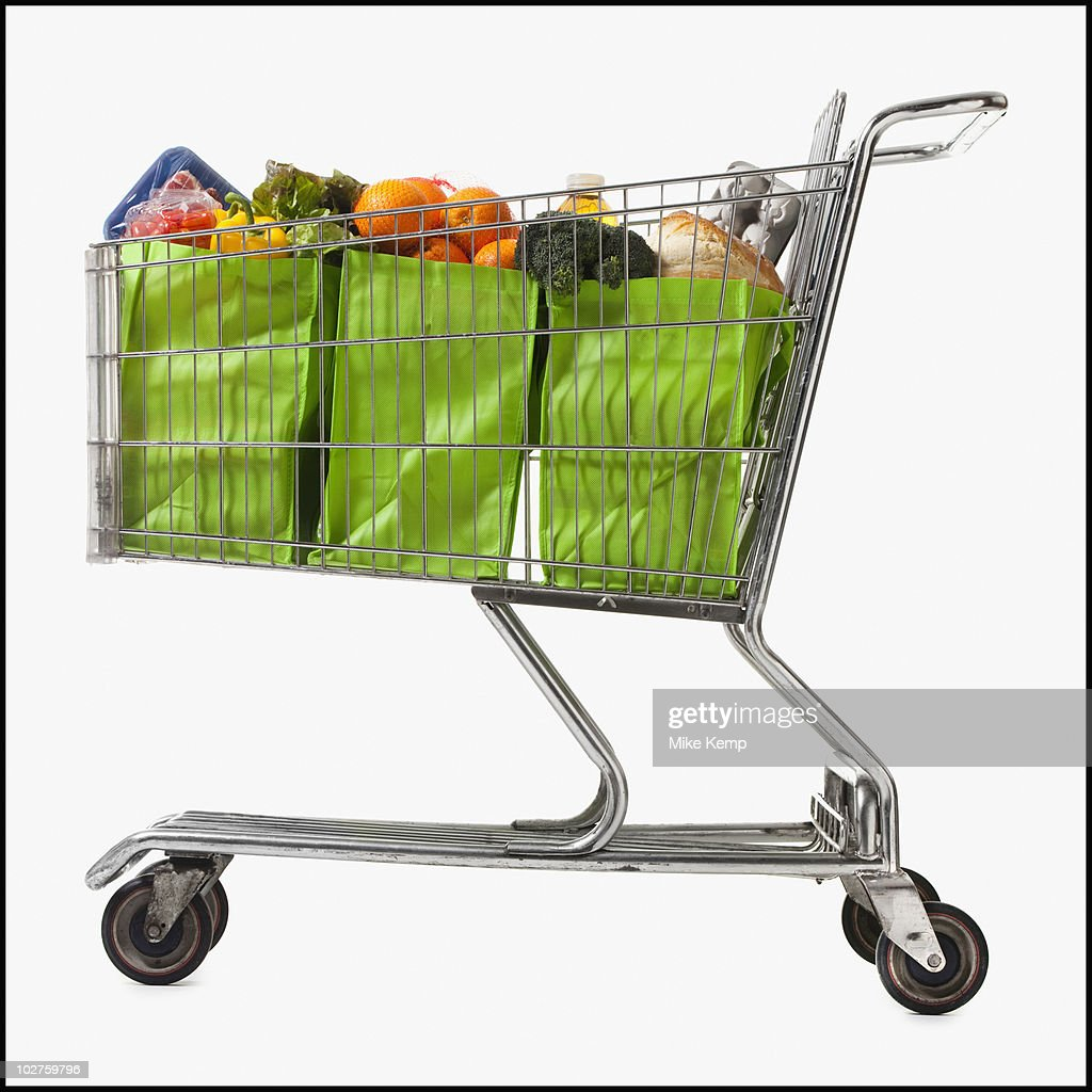 Grocery cart full of bags of groceries : Stock Photo