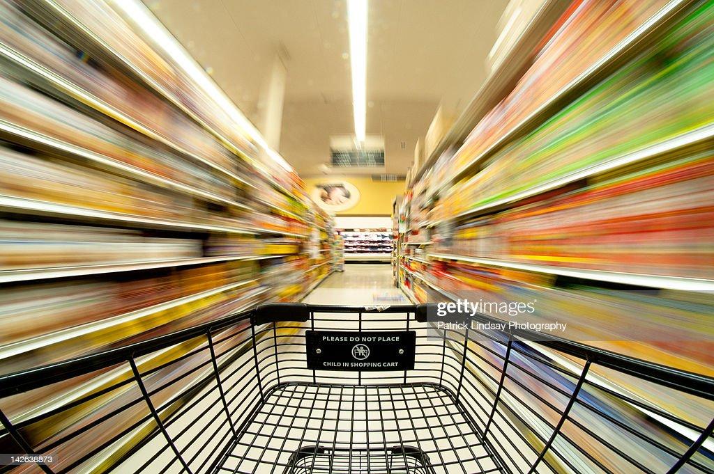 Grocery cart moving down aisle : Bildbanksbilder
