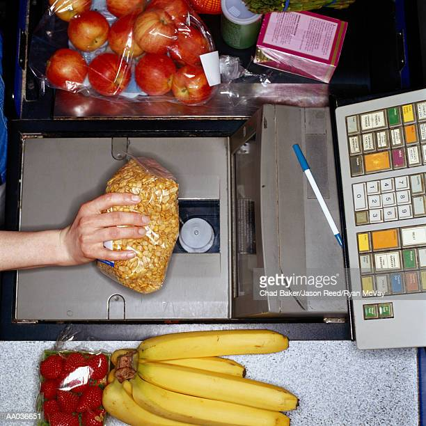 Grocery clerk scanning items at checkout counter, overhead view