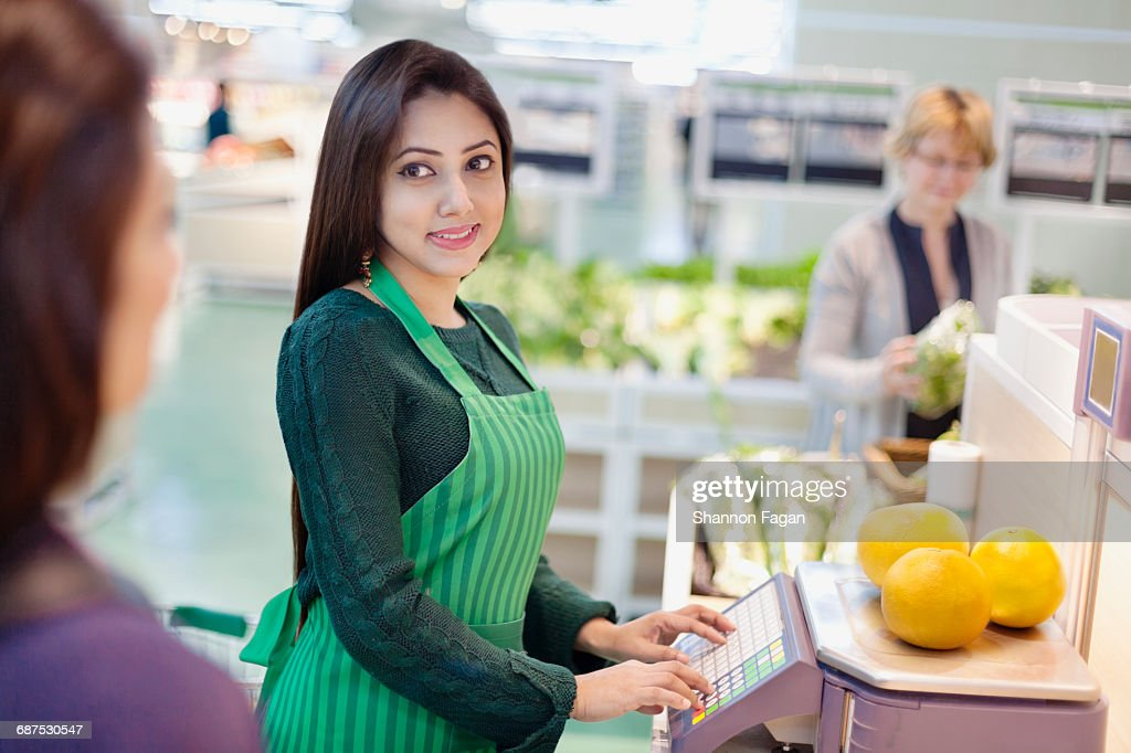 grocery clerk weighing produce in supermarket high