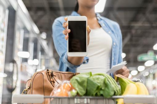 Grocery shopper shows blank screen on smart phone - gettyimageskorea