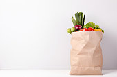Grocery shopping bag with food on gray background