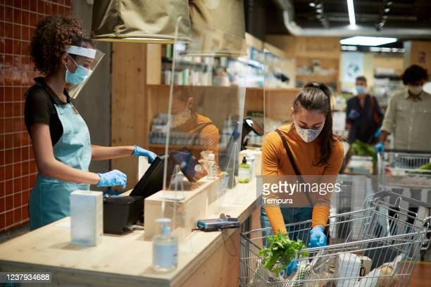 grocery shopping check out with a customer and a cashier. - coronavirus protection stock pictures, royalty-free photos & images