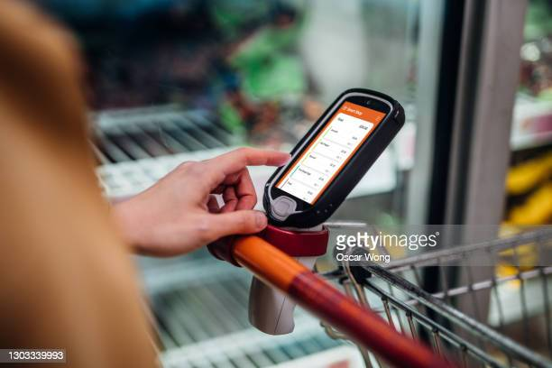 grocery shopping with a smart handset - shop stock pictures, royalty-free photos & images
