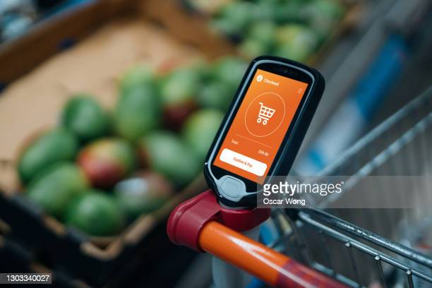 grocery shopping with a smart handset - merchandise stock pictures, royalty-free photos & images