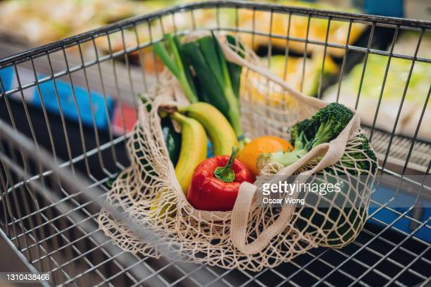 grocery shopping with reusable shopping bag at supermarket - vegetable stock pictures, royalty-free photos & images