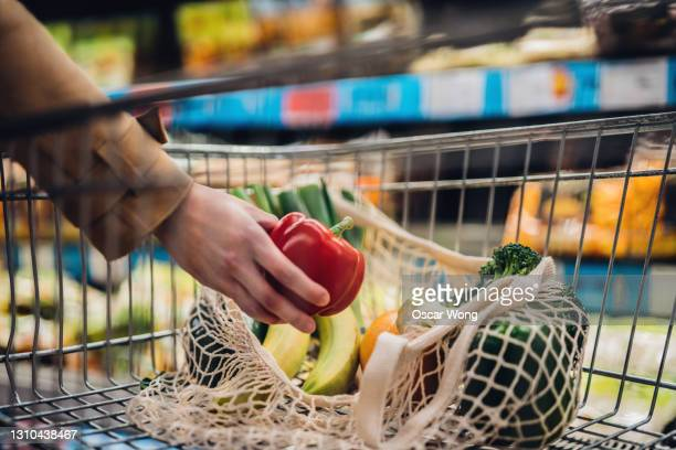 grocery shopping with reusable shopping bag at supermarket - sustainable lifestyle stock pictures, royalty-free photos & images