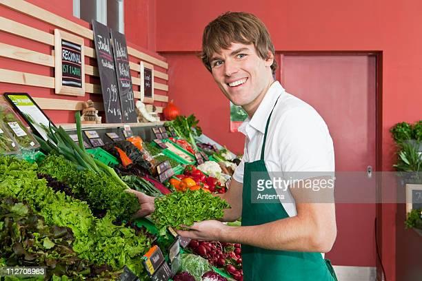 A grocery stocker stocking leaf lettuce