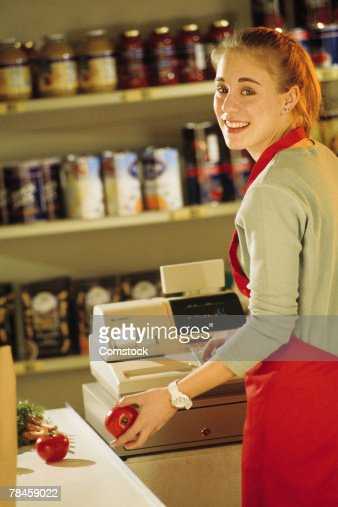 Grocery Store Clerk At Cash Register High Res Stock Photo