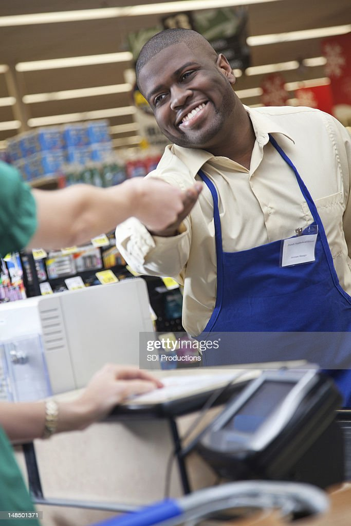 Grocery store clerk handing change back to customer at checkout : Stockfoto