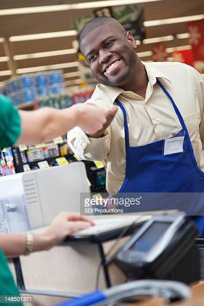 Grocery store clerk handing change back to customer at checkout