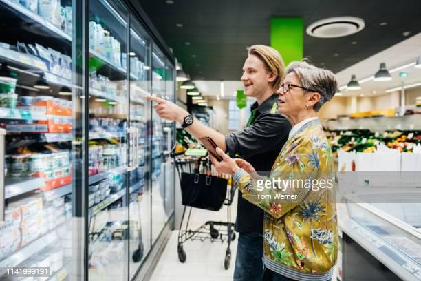grocery store clerk helping senior woman with food item - mithilfe stock-fotos und bilder