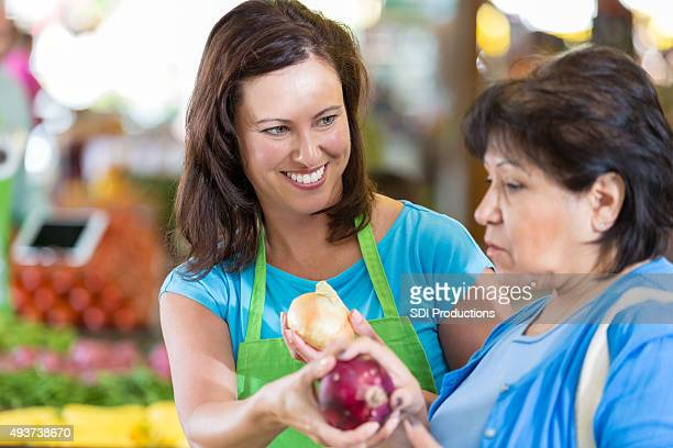 Grocery store employee assisting senior customer in produce section