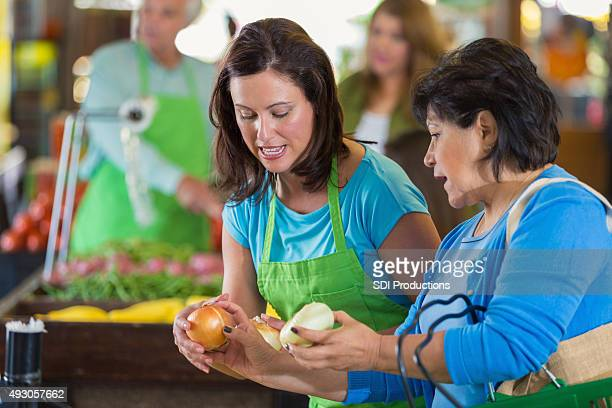 Grocery store employee assisting senior customer with produce selection