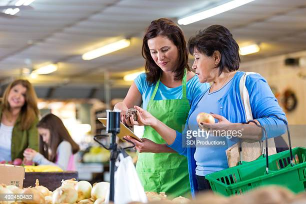 Empleado de las tiendas de comestibles ayudando a cliente con Pedidos en línea
