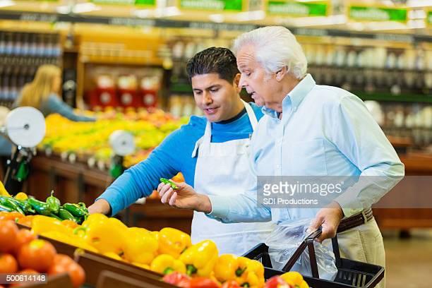 Loja de mercearia funcionário ajudando sénior de compras em produzir secção