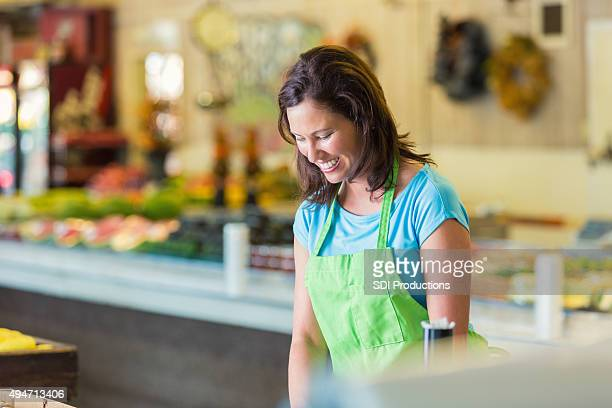 Grocery store employee stocking produce aisle
