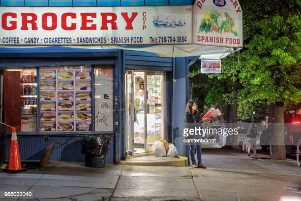 grocery store in queens on a rainy night - fachada supermercado imagens e fotografias de stock