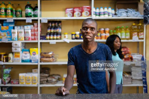 Grocery store owner Blessing Mushonga poses for a portrait inside his shop in Rimuka township Kadoma on January 24 2019 In the central Zimbabwean...