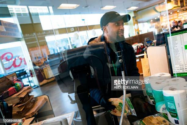 A grocery store worker checks out a customer behind a newly installed sneeze and cough guard at a MOM's Organic Market on April 2 2020 in Washington...