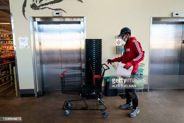 A grocery store worker sanitizes a shopping cart at a MOM's Organic Market on April 2 2020 in Washington DC