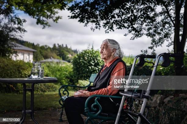 Großmutter mit Rollator sitzt auf Parkbank