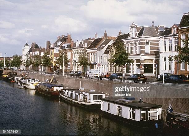 Hausboote liegen auf einem Kanal der alten Hansestadt oberhalb der Kaimauer verläuft eine Straße und Wohnhäuser reihen sich aneinander Aufgenommen um...