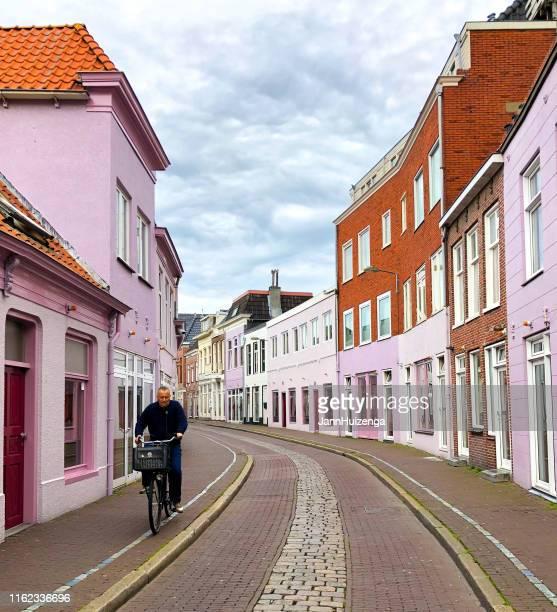 groningen, nederland: fietser rijdt door rosse wijk - groningen stockfoto's en -beelden