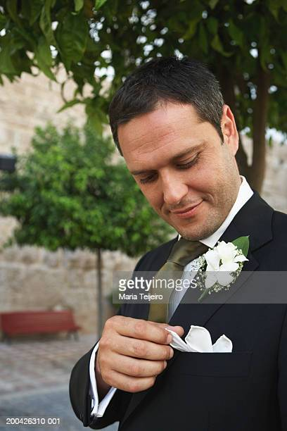 Groom adjusting handkerchief in jacket pocket