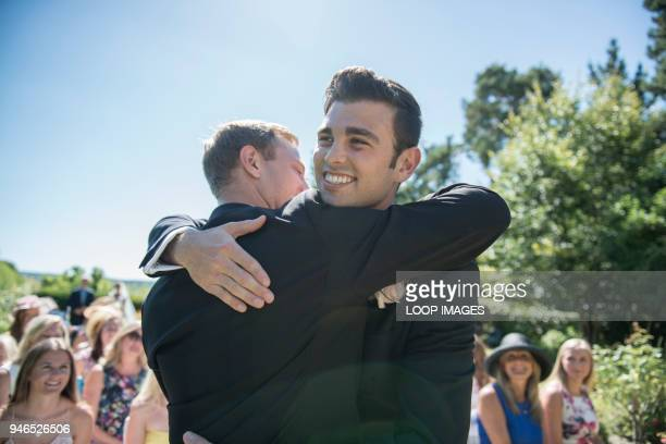 A groom and best man share a hug prior to the wedding service