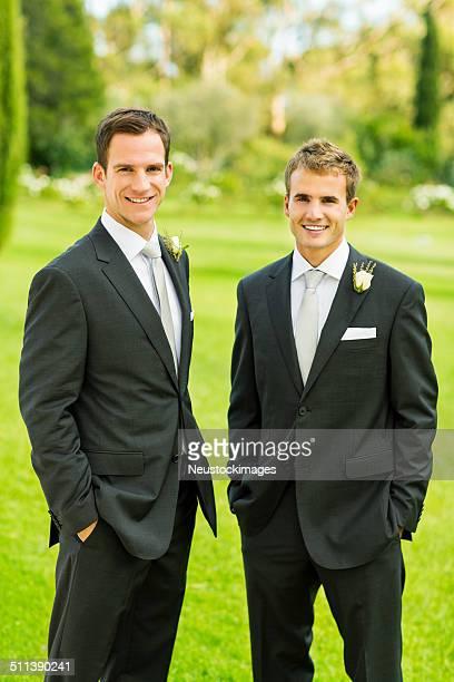 Marié et meilleurs homme debout ensemble dans le jardin