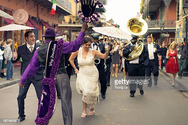 "Groom and bride and the wedding party join in the procession ""second lining"" down Royal Street in the French Quarter in New Orleans."