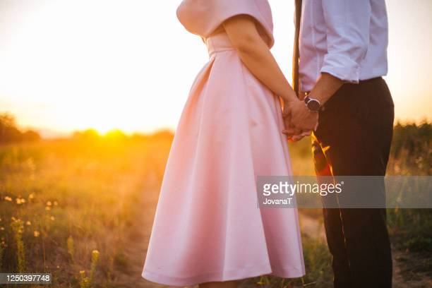groom and bride holding their hands on sunset light - wedding dress stock pictures, royalty-free photos & images