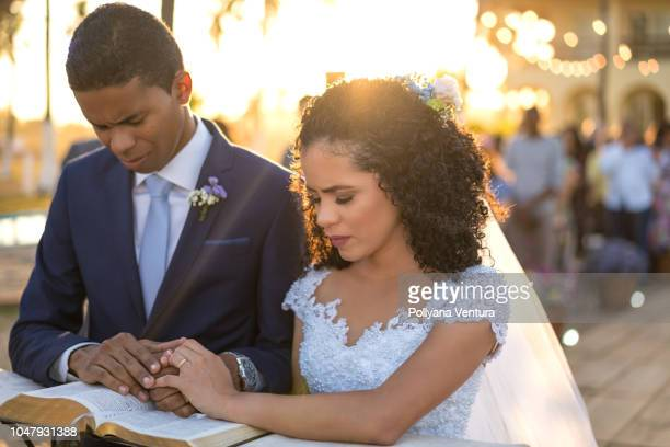groom and bride kneeling praying - wedding vows stock pictures, royalty-free photos & images