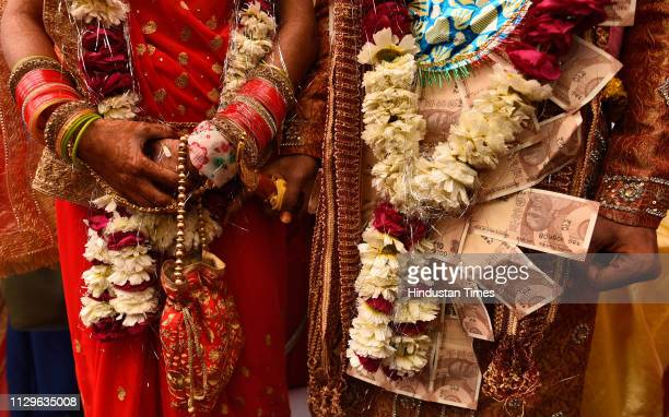 A groom and bride stand after performing rituals during a mass wedding for eight couples at Hanuman Vatika Ramleela Maidan on March 8 2019 in New...