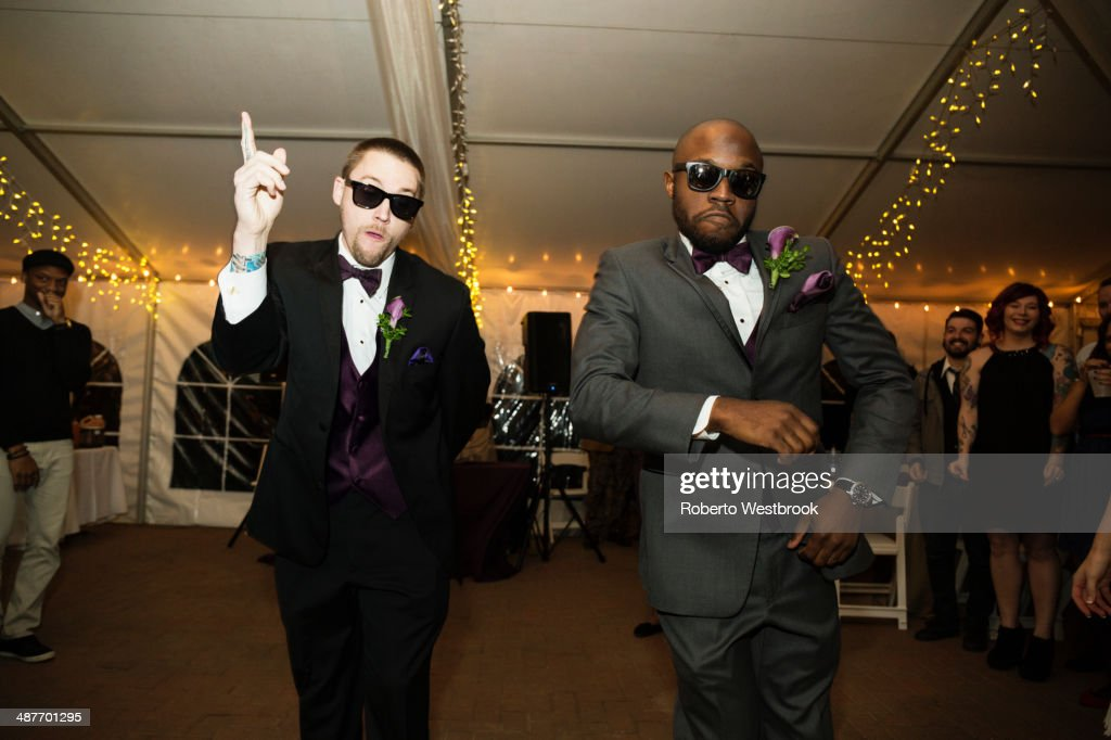 Groom and groomsman dancing at reception : Stock Photo