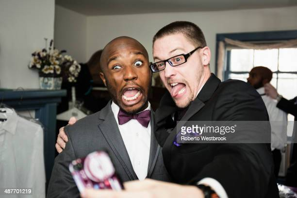 Groom and groomsman taking silly self-portrait