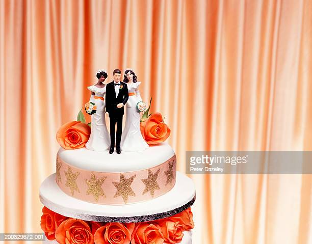 Groom and two bride figurines on top of wedding cake, close up