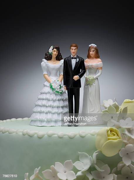 groom and two bride figurines on top of wedding cake - wedding cake figurine stock pictures, royalty-free photos & images