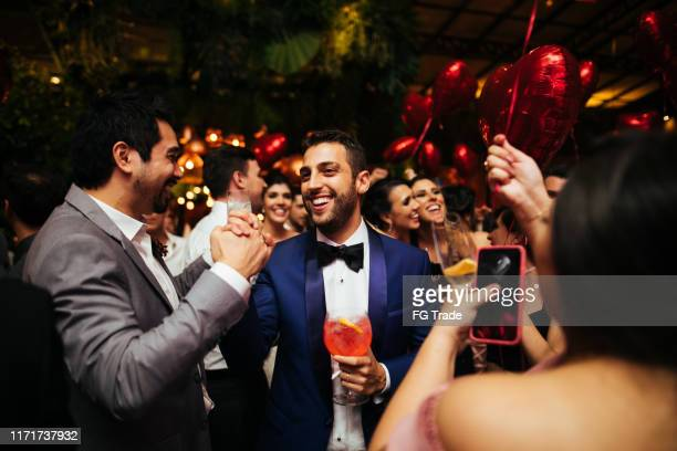 groom and wedding guests laughing during party - dance floor stock pictures, royalty-free photos & images