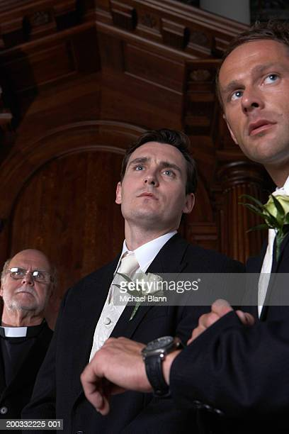 Groom, Best man and vicar waiting in church, Best man checking watch
