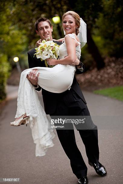 Groom carring Bride smiling park path wearing wedding gown tux
