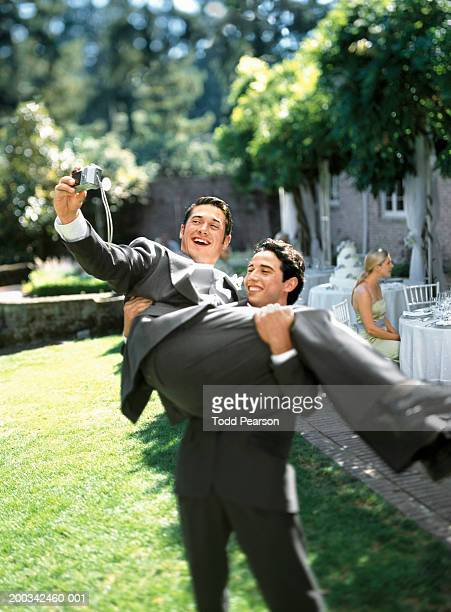 Groom carrying best man, best man photographing himself, smiling