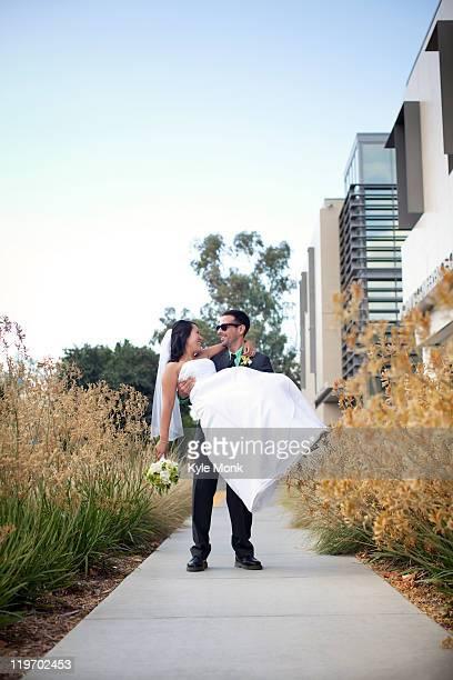 Groom carrying bride on sidewalk