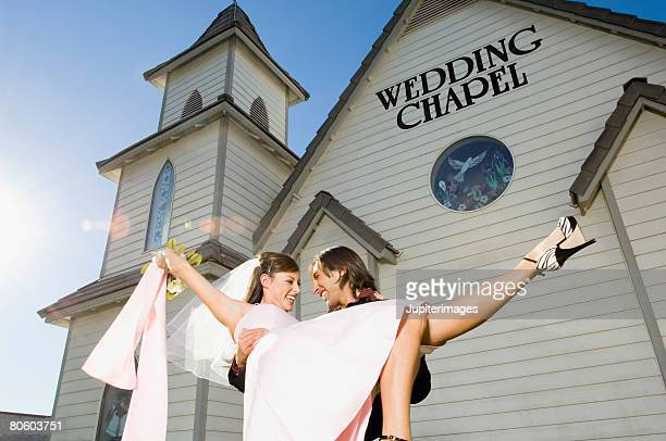 Groom carrying bride out of chapel