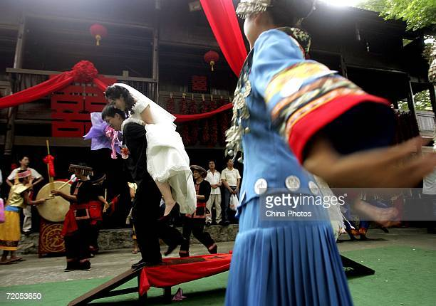 A groom carrying the bride on his back walks on a door plank during a collective wedding ceremony held in a folk village on September 30 2006 in...