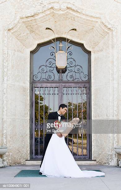 Groom dipping bride in front of church