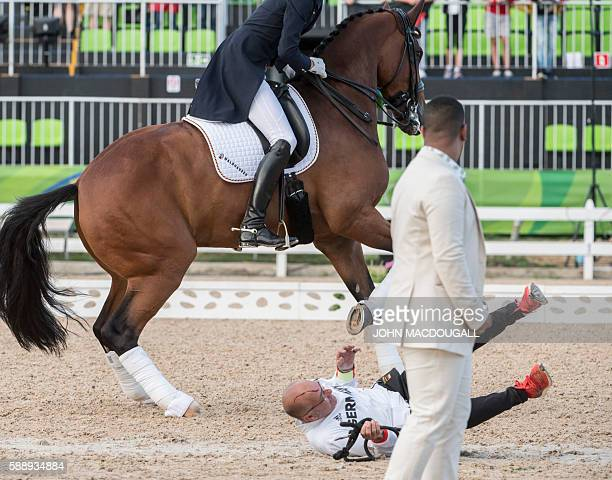 Groom falls to the ground after Germany's Sonke Rothenberg's horse Cosmo hit him in the head during the victory ceremony of the Equestrian's Dressage...